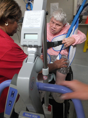 Staff using the hoyer lift to transfer a resident